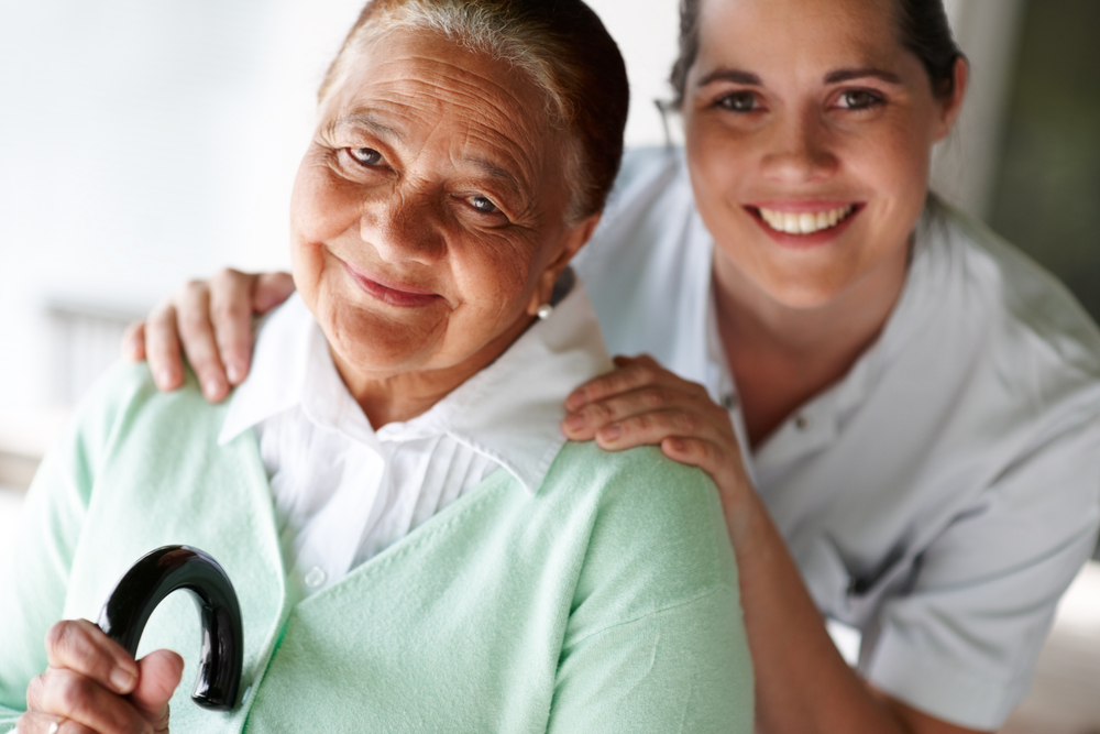 medical staff with elderly female patient smiling